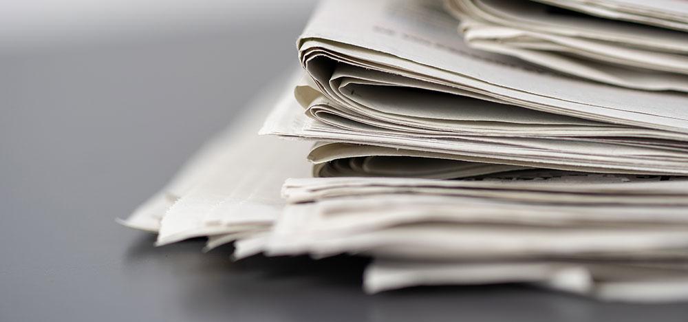 Pile-De-Journaux Sur-Une-Table-Blanche